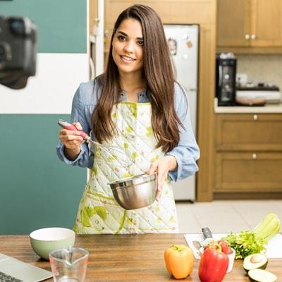 Женщина-блогер готовит еду, снимает на фотоаппарат кулинарный блог
