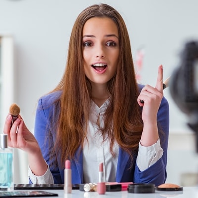 Женщтна бьюти-блогер рассказывает на камеру про макияж