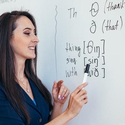 Женщина-учитель объясняет английский язык на доске