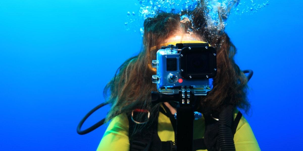 Женщина снимает видео на экш-камеру под водой
