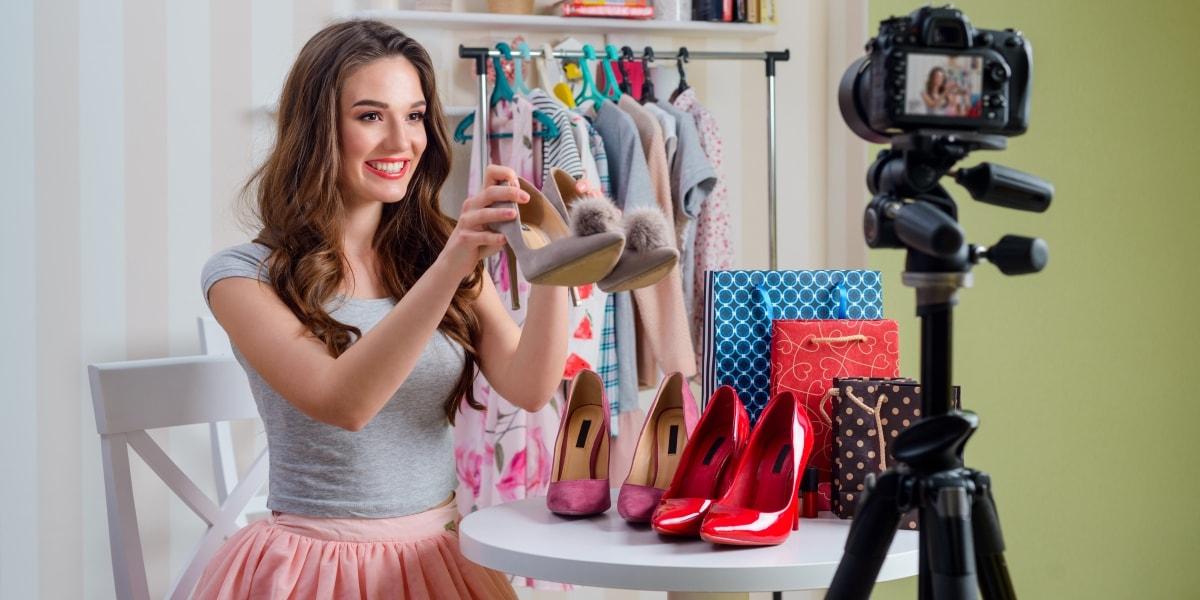 Женщина снимает блог об одежде, фотоаппарат на штативе