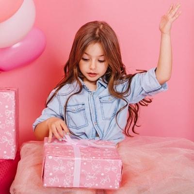 Девочка ребёнок распаковывает подарок, открывает коробку