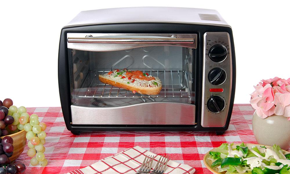 Мини-печь стоит на кухне, внутри бутерброд