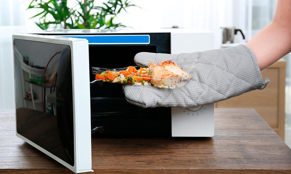 Микроволновка принимает в себя пищу, рука в прихватке