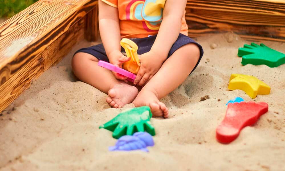 Ребёнок играет в песочнице